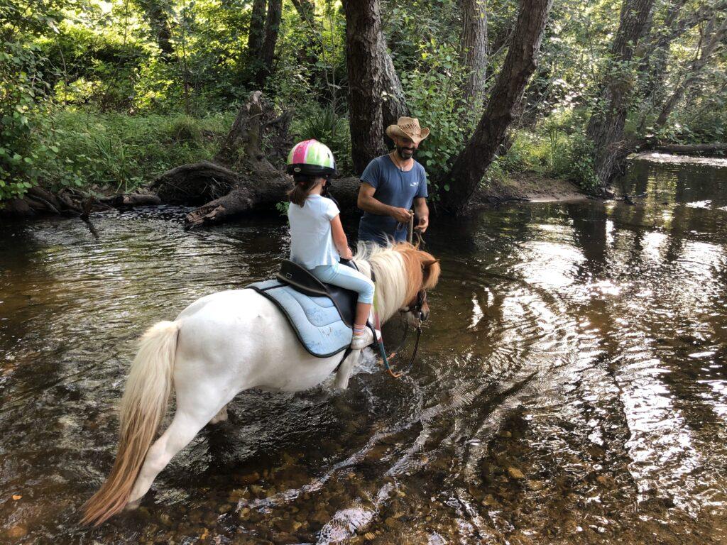 Giuseppe con pony e bimba nel fiume